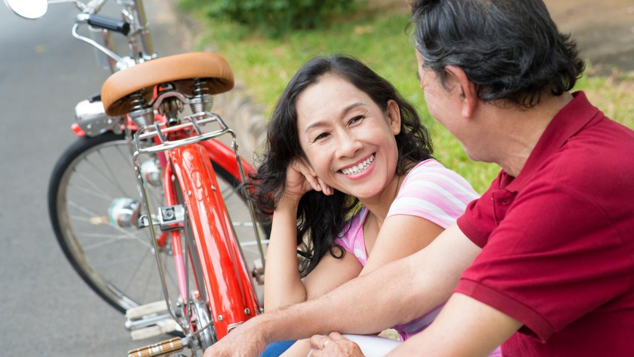 Pareja sonriendo con una bicicleta