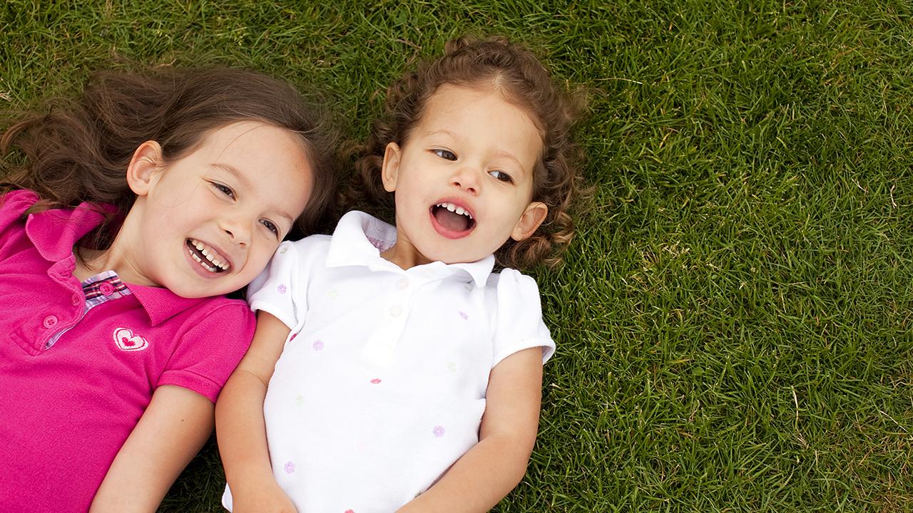 dos niñas echadas en el pasto