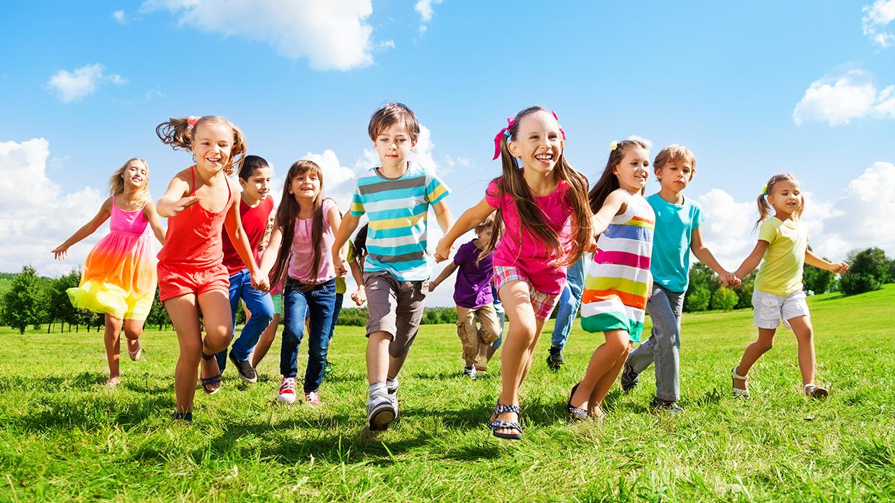 niños corriendo en el pasto