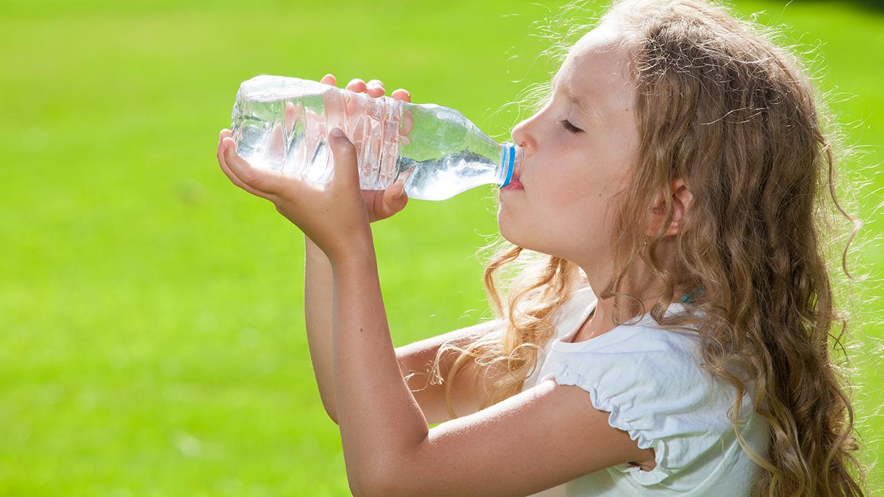 niña bebe agua de una botella