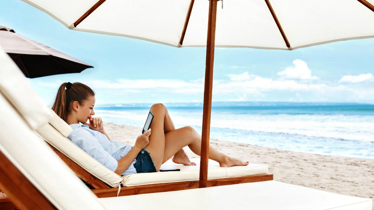 mujer leyendo en la playa bajo una sombrilla