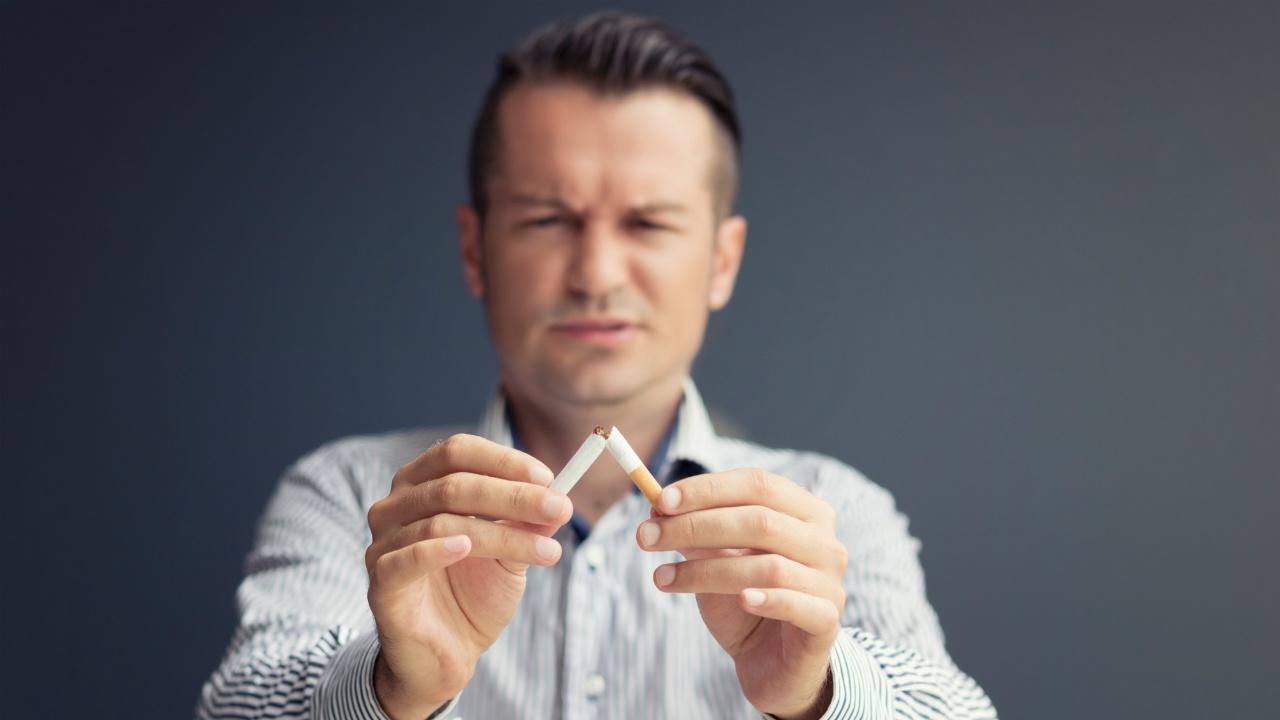 hombre rompiendo cigarrillo