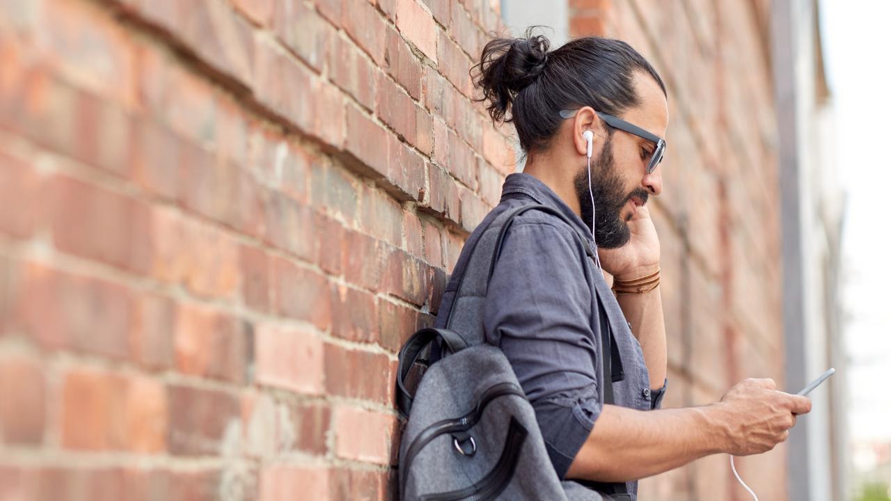 hombre escuchando musica en una pared