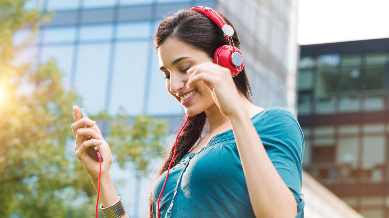 mujer joven escuchando musica en la calle