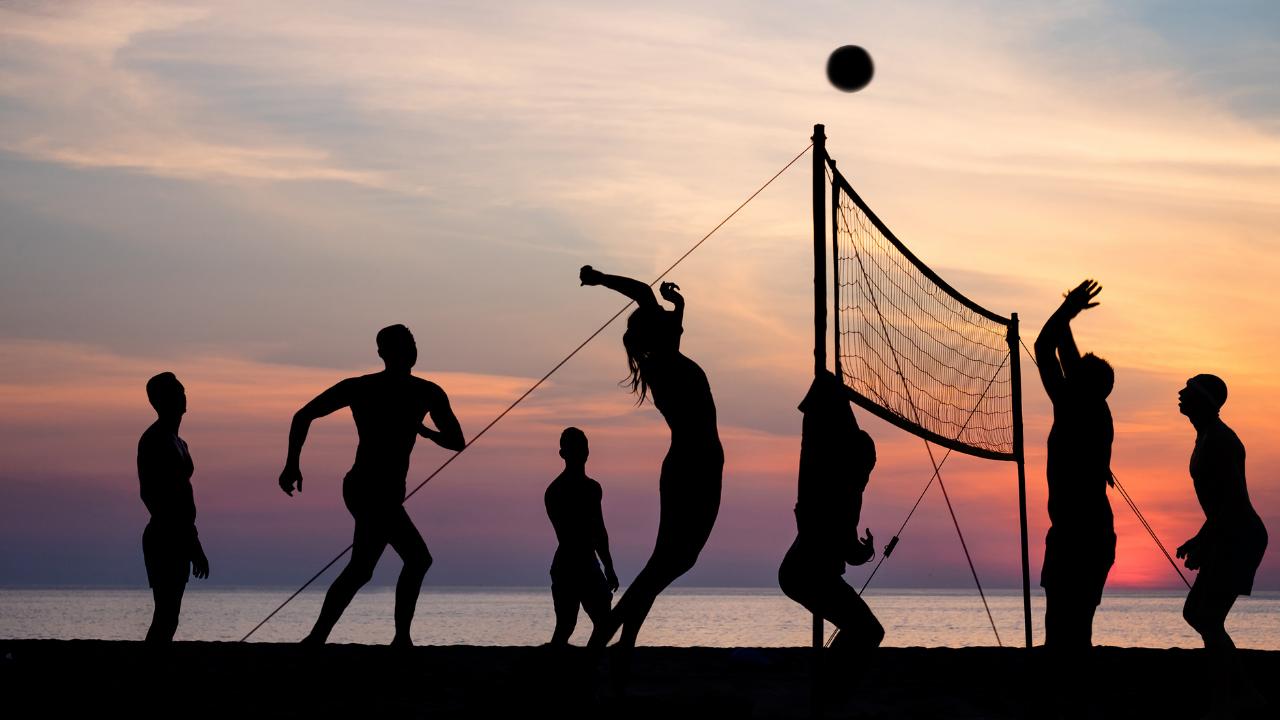 jovenes jugando volleyball en la playa