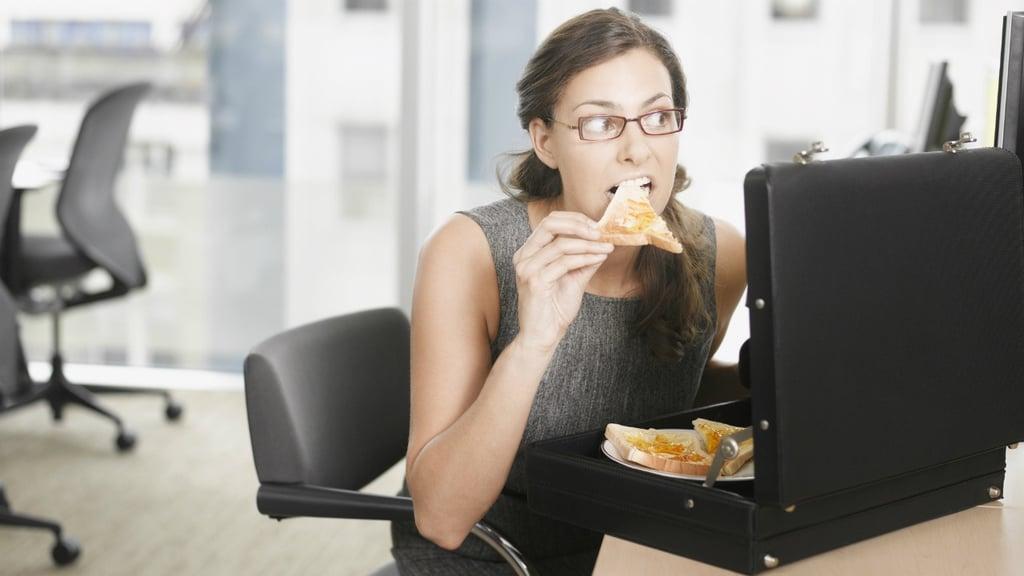mujer comiendo en su oficina