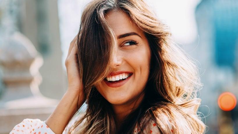 mujer riendo con el pelo sobre el rostro