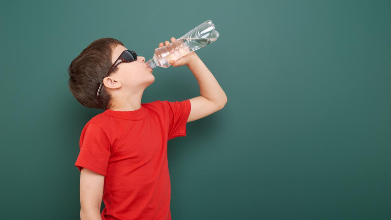 niño tomando agua de una botella