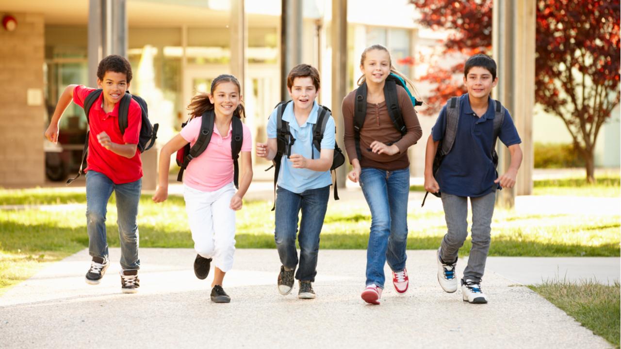 niños con sus mochilas corriendo en el colegio