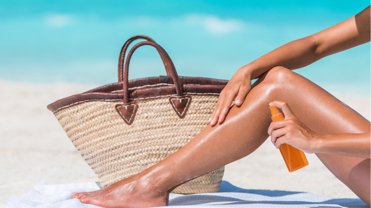 mujer echandose bronceador en las piernas