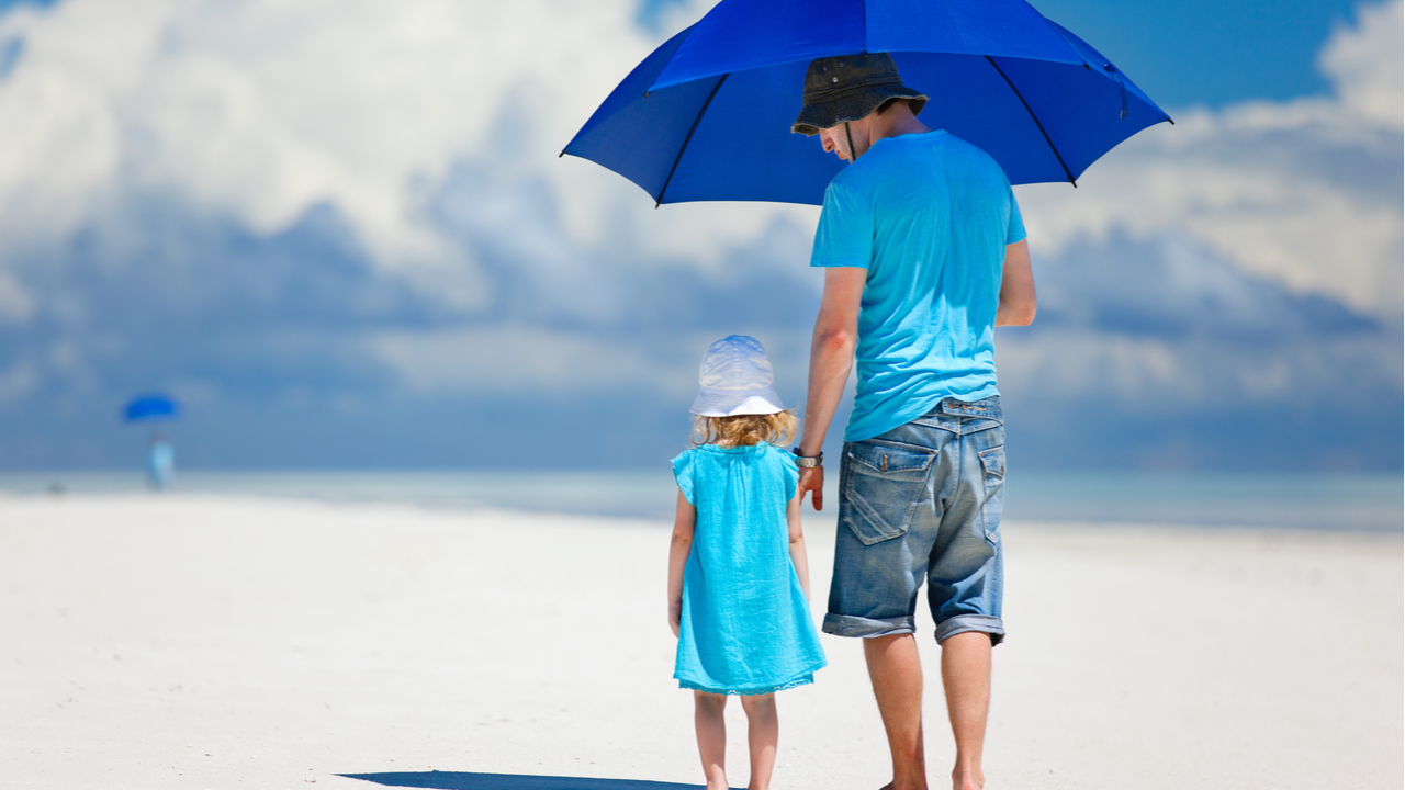 padre e hija caminando por la playa