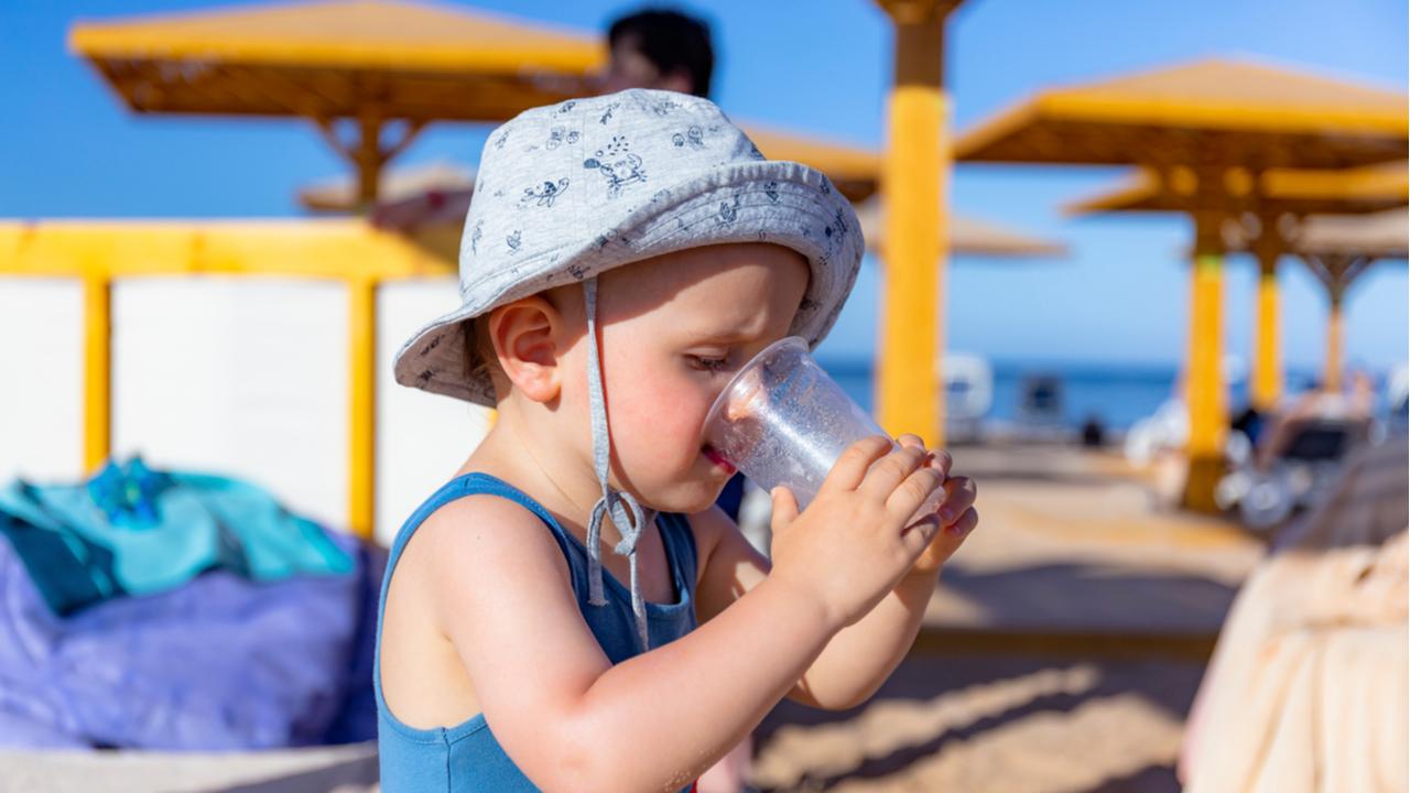 bebe tomando agua en la playa