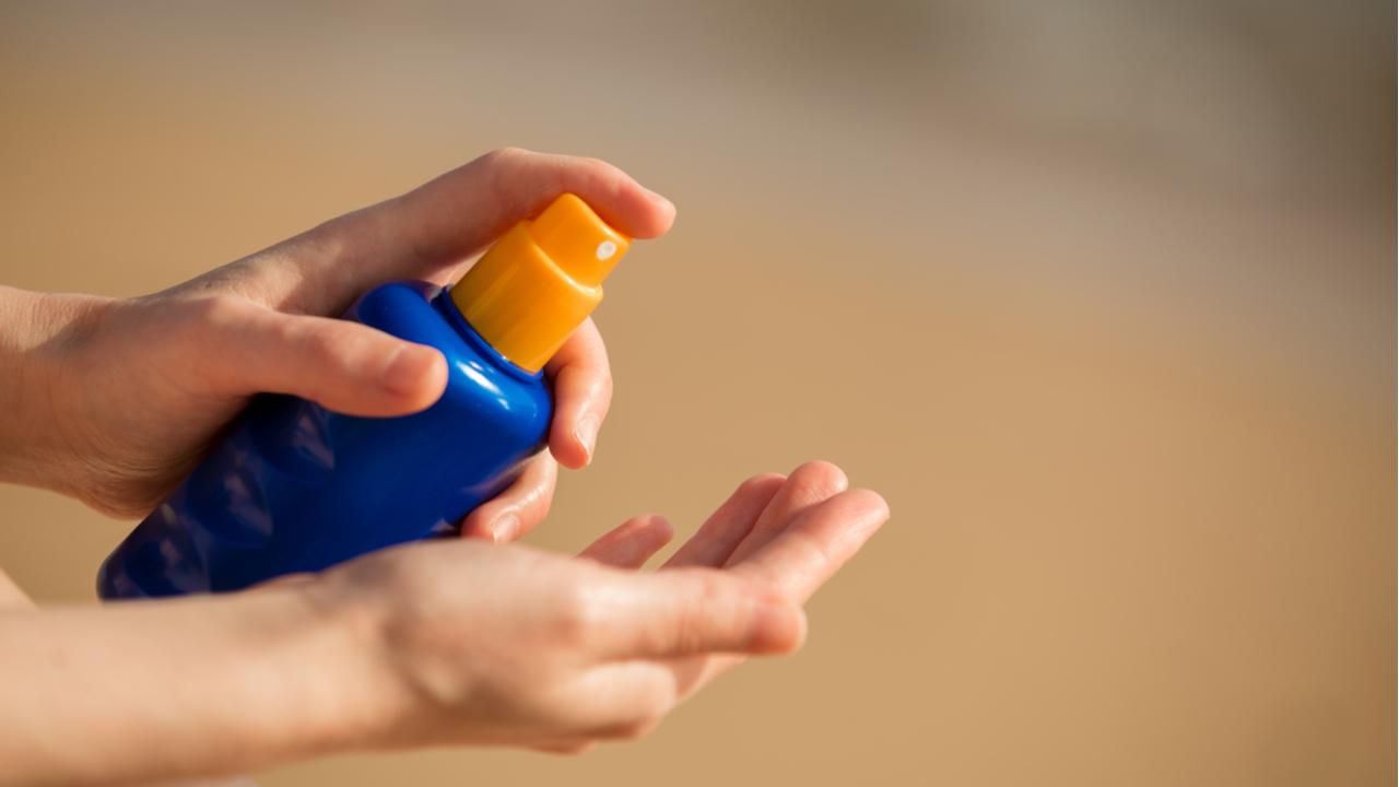 persona aplicando bloqueador solar en su mano