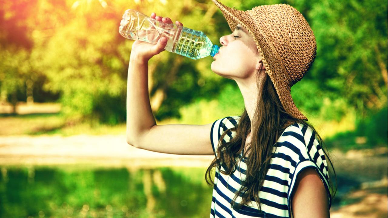 mujer tomando agua bajo el sol