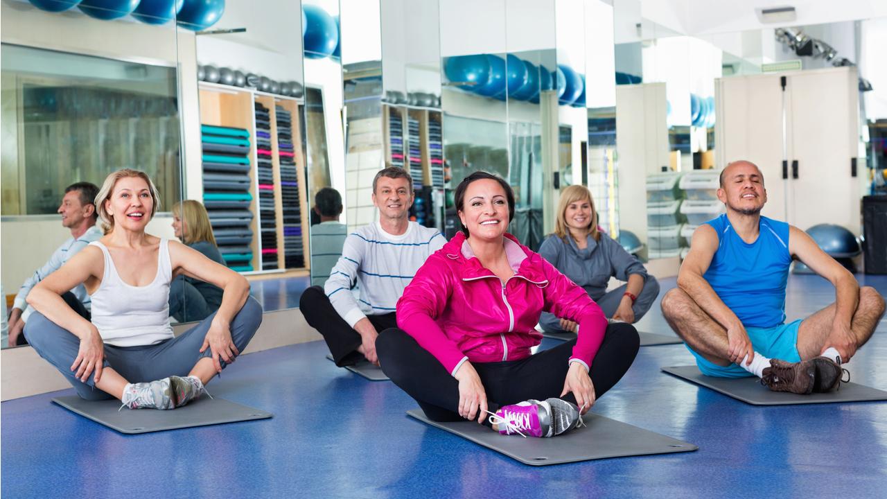 adultos con mat haciendo yoga
