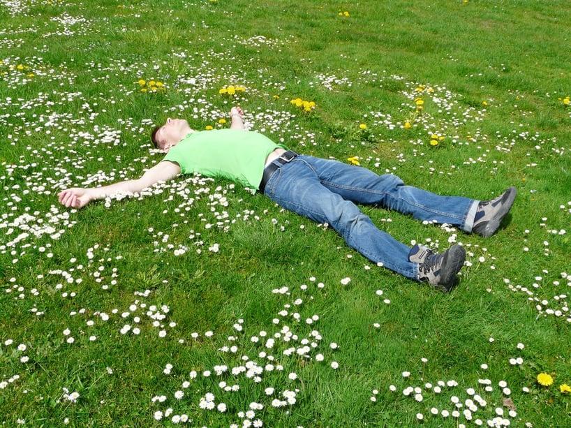 hombre relajado echado en campo de flores