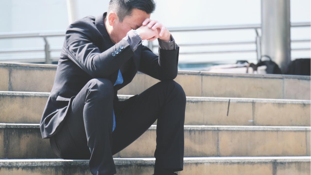 hombre sentado en las escaleras pensando