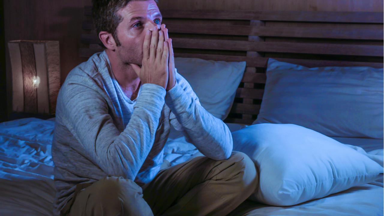 hombre abrumado sentado en su cama