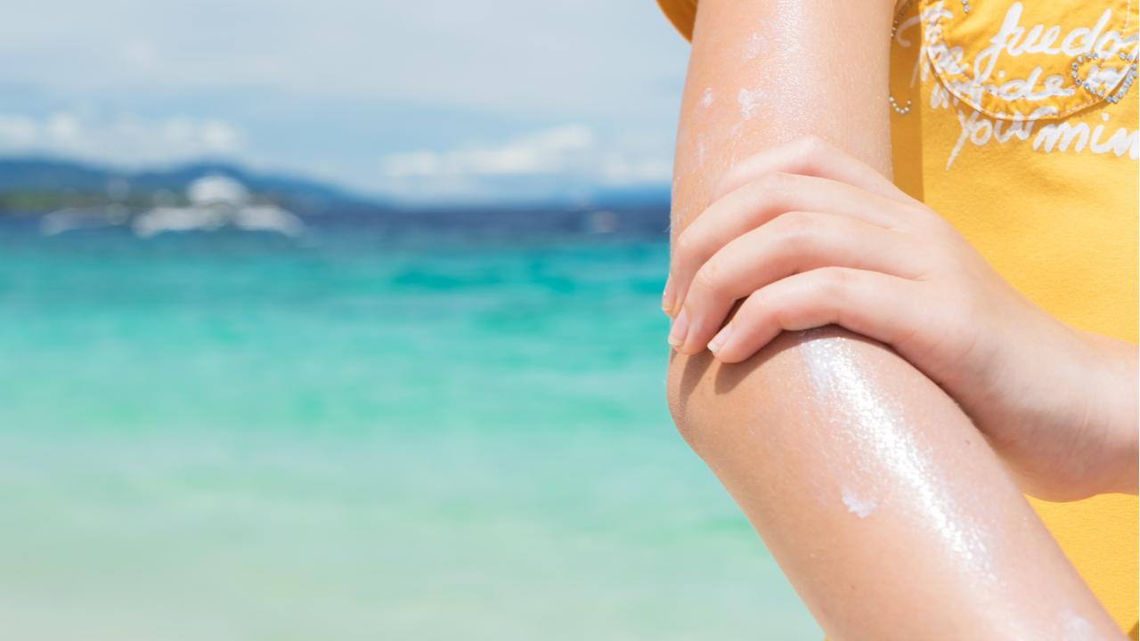 joven aplicandose protector solar a la piel