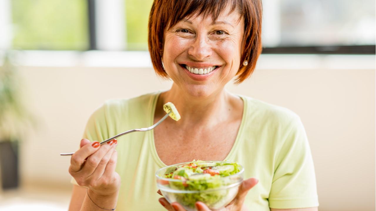 mujer de edad media come ensalada