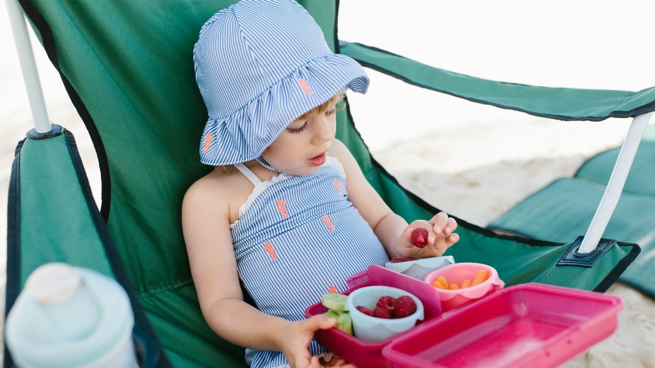 niña comiendo fruta en verano
