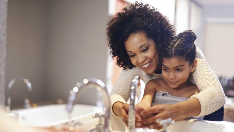 madre lava las manos a su hija