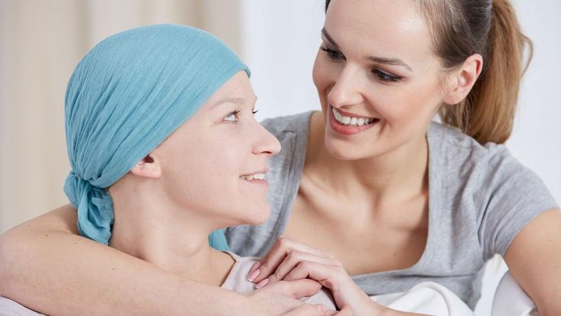 mujer abraza a mujer con cancer