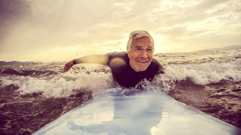 hombre mayor haciendo surf