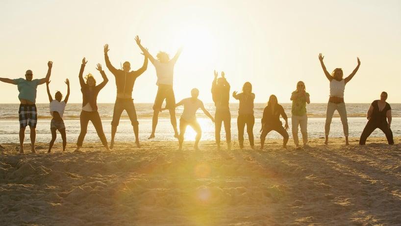 grupo de amigos en la playa saltan