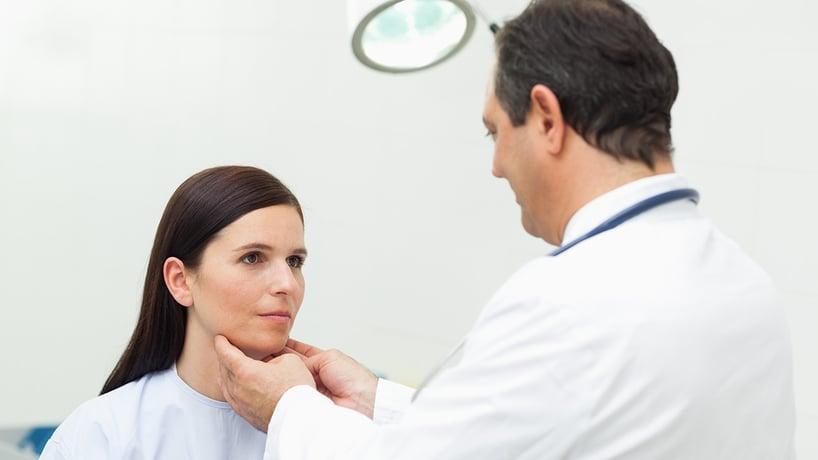 doctor examinando la garganta de mujer paciente