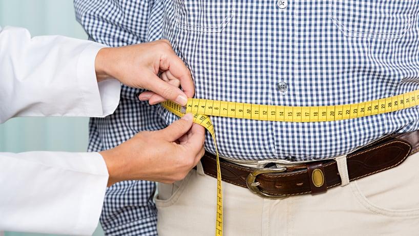 doctora midiendo la cintura de una persona obesa