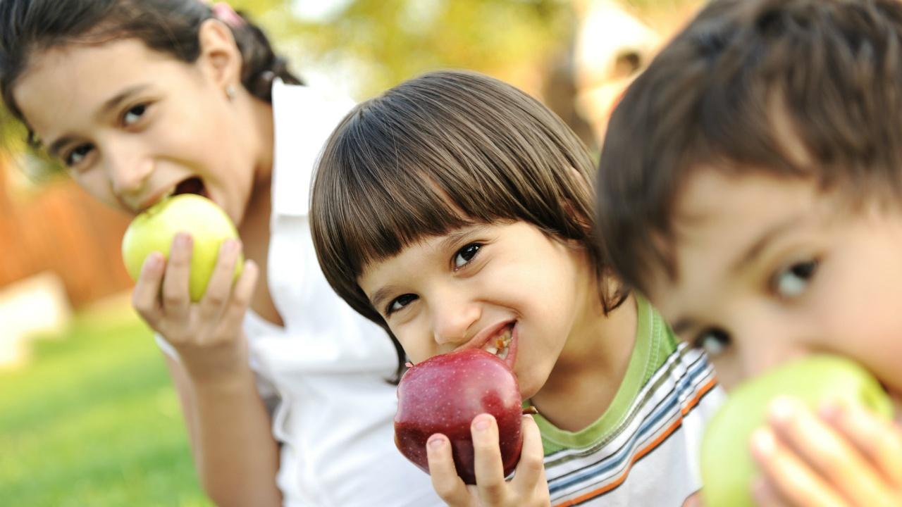 tres niños comiendo manzanas