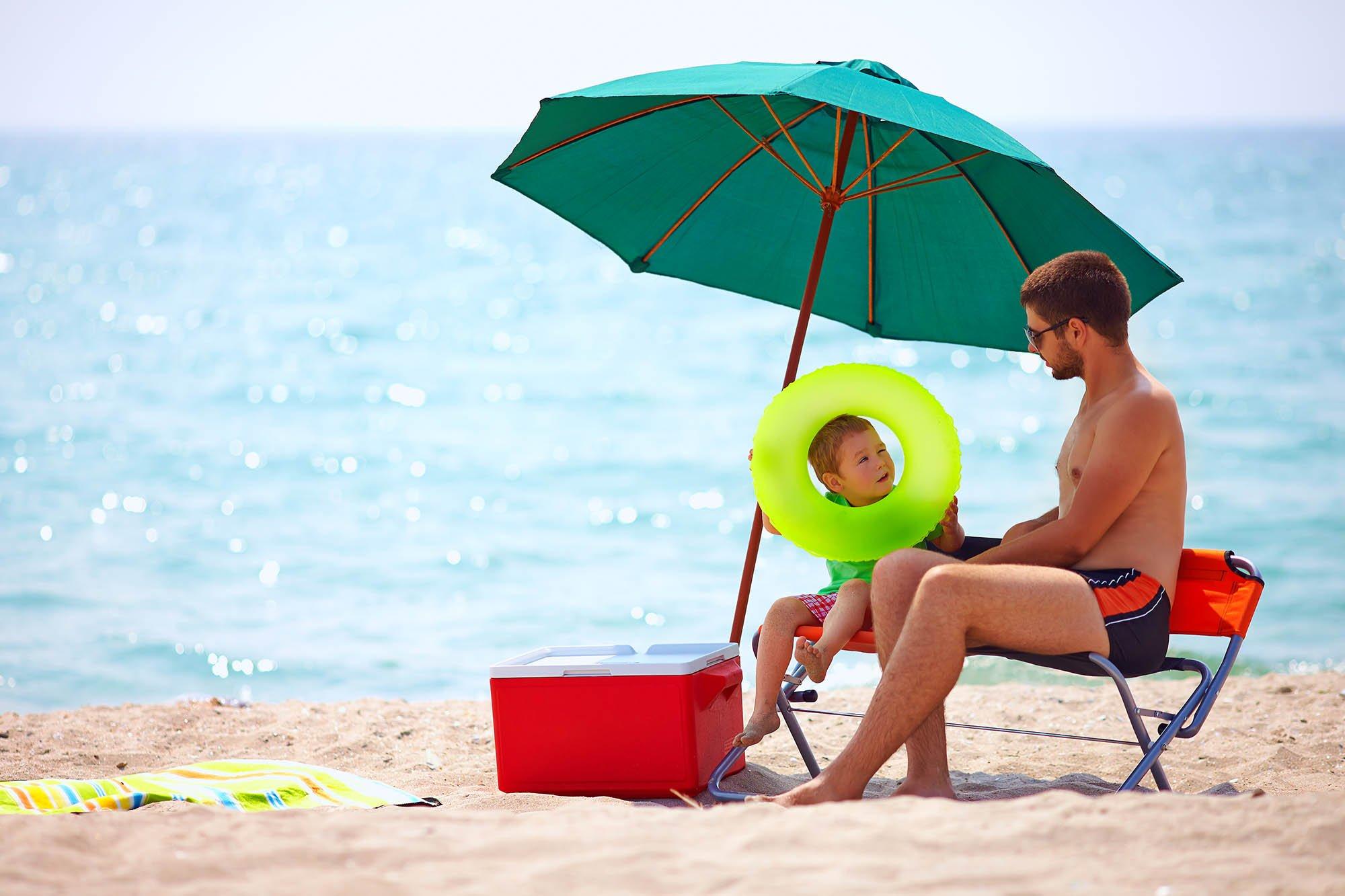papa e hijo en la playa con cooler