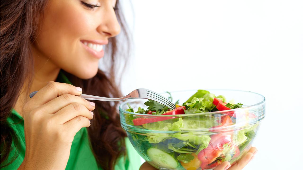 mujer sonrie mientras come ensalada
