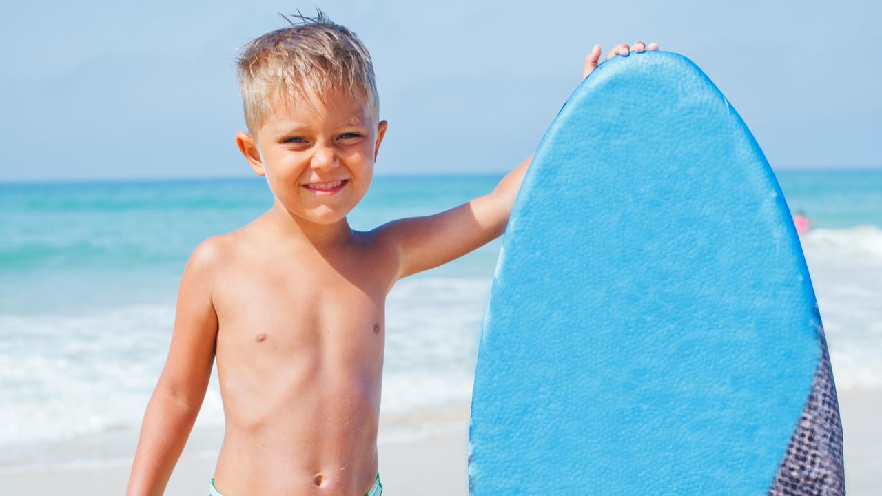 niño tablista en la playa