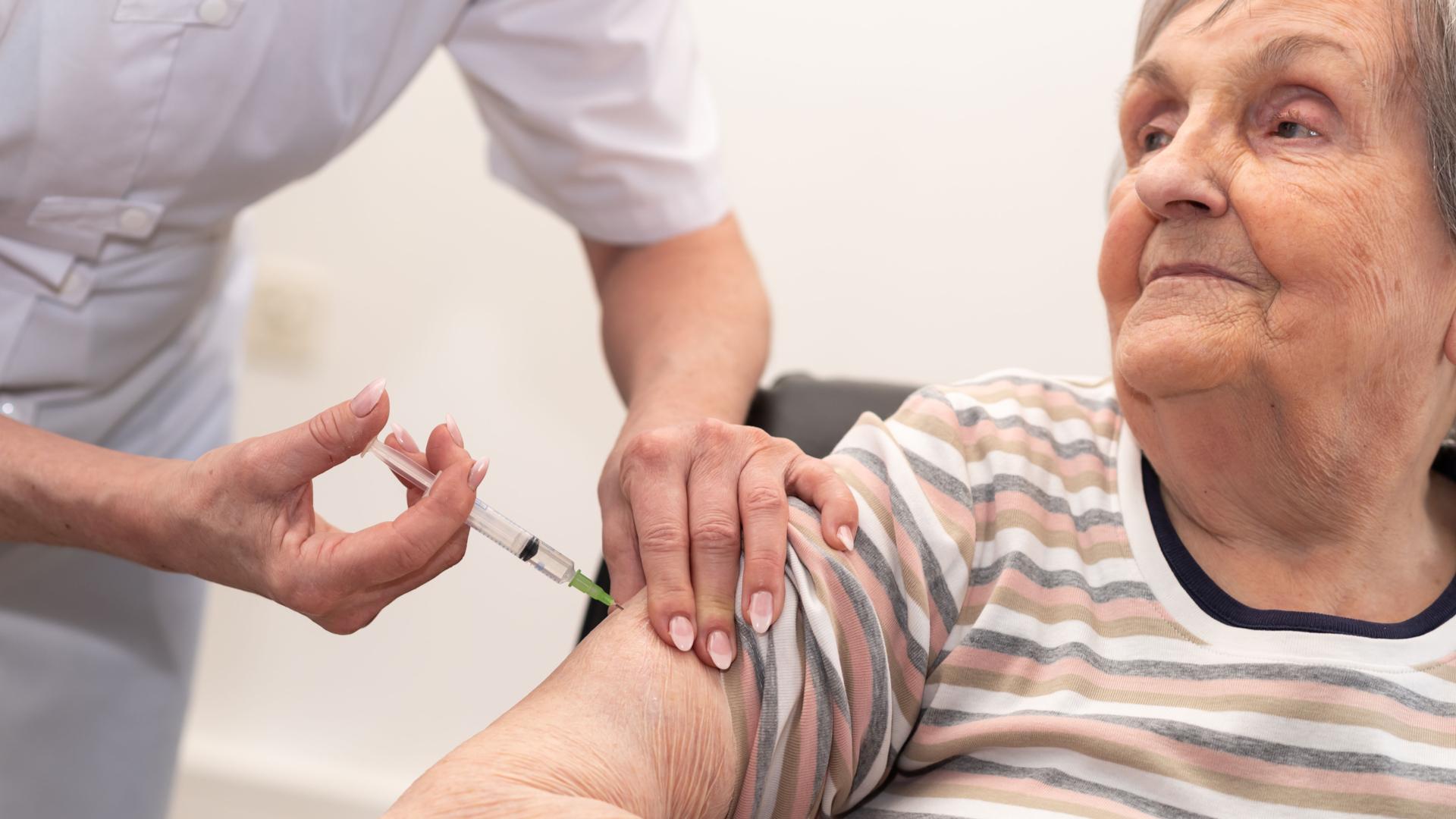 enfermera vacunando a adulto mayor