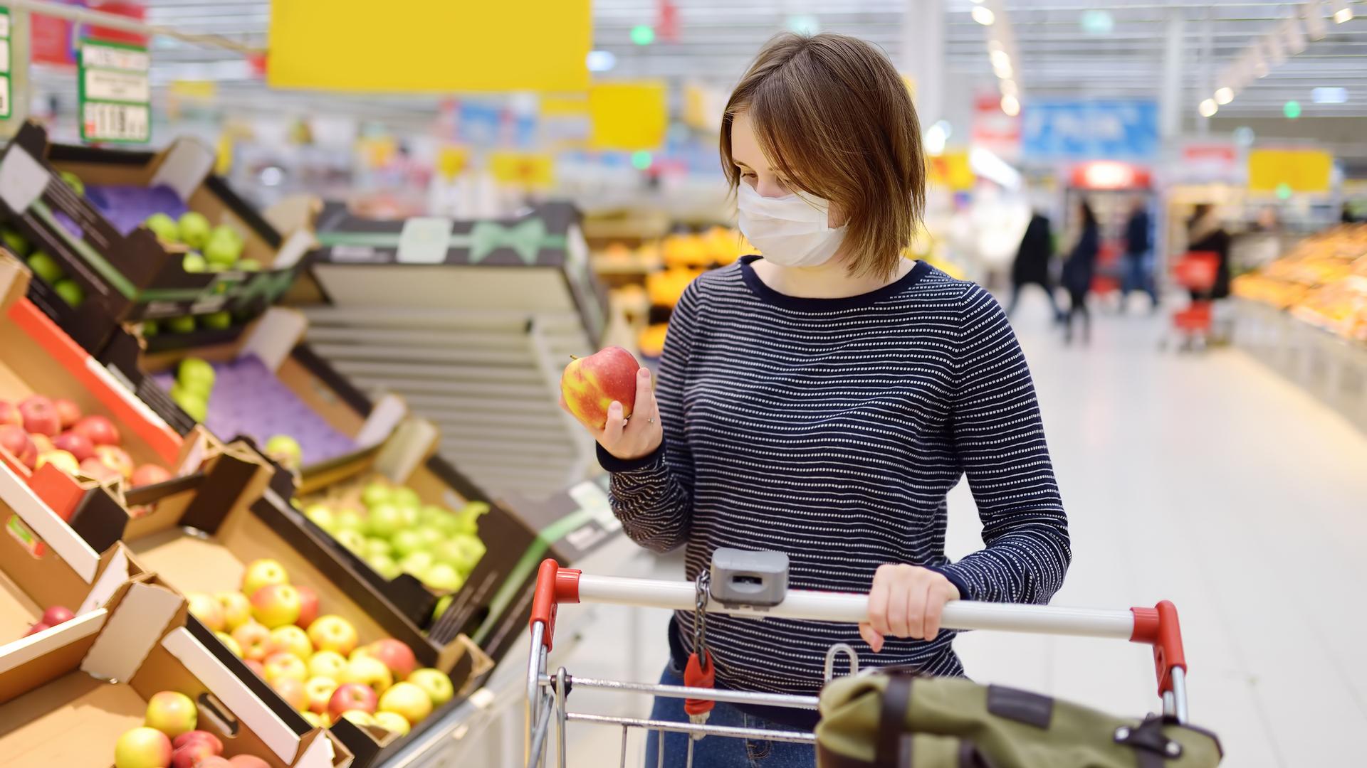 mujer comprando en supermercado con mascarilla