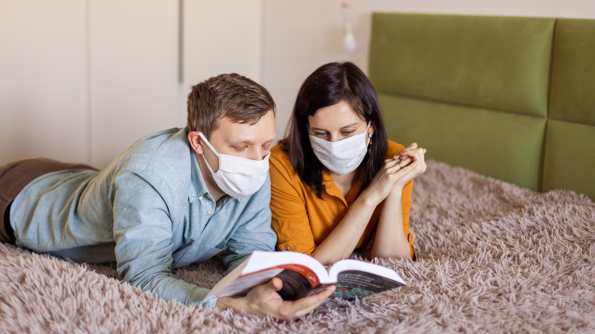 pareja leyendo en la cama con mascarillas