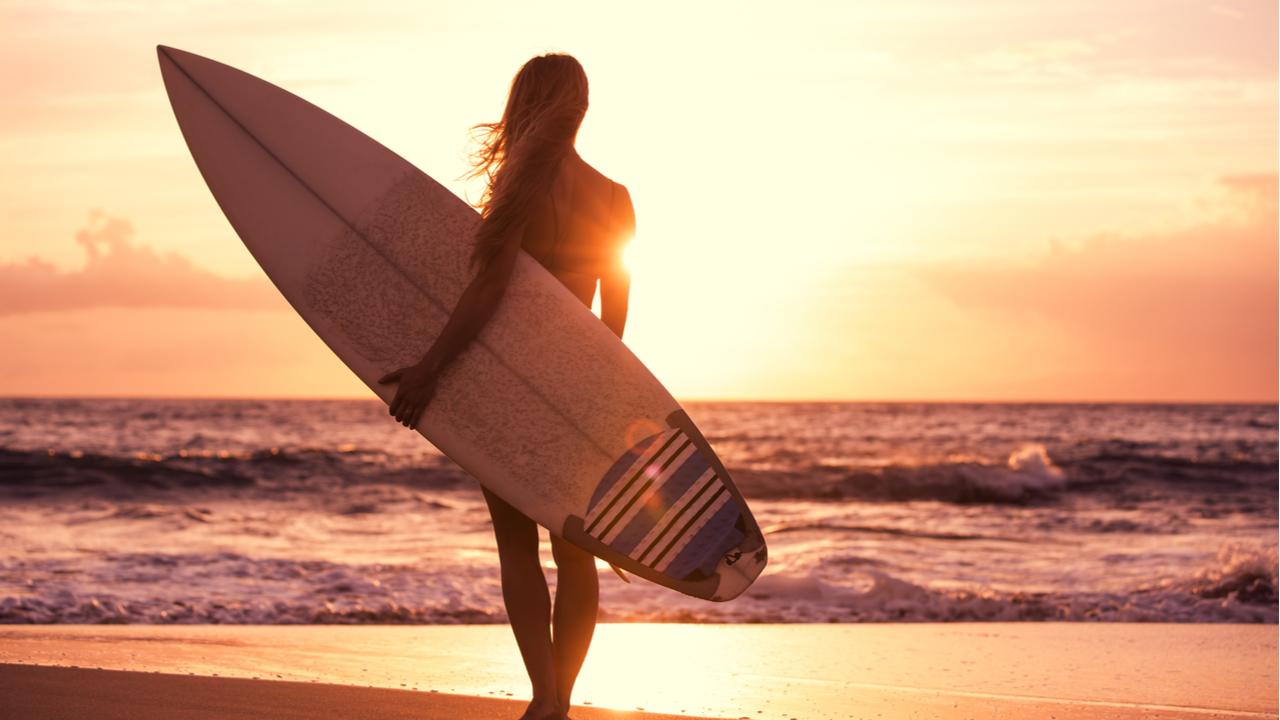 mujer hace surf en el sunset