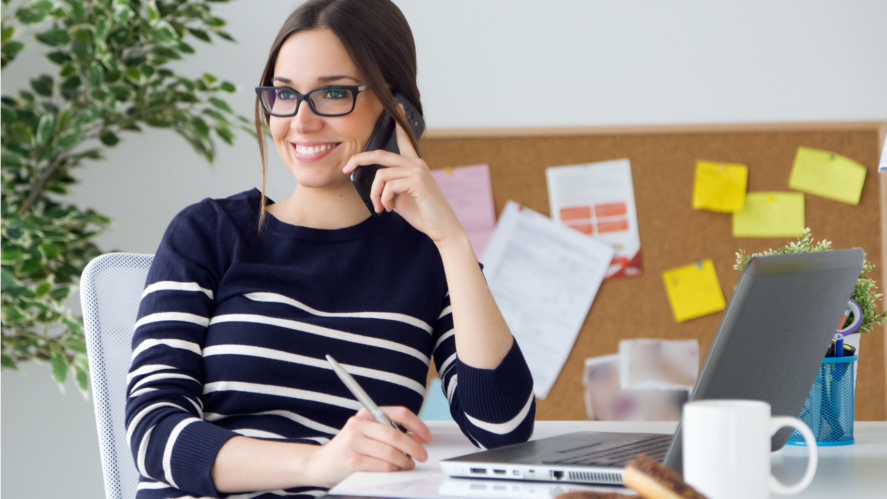 mujer sonriente habla por teléfono