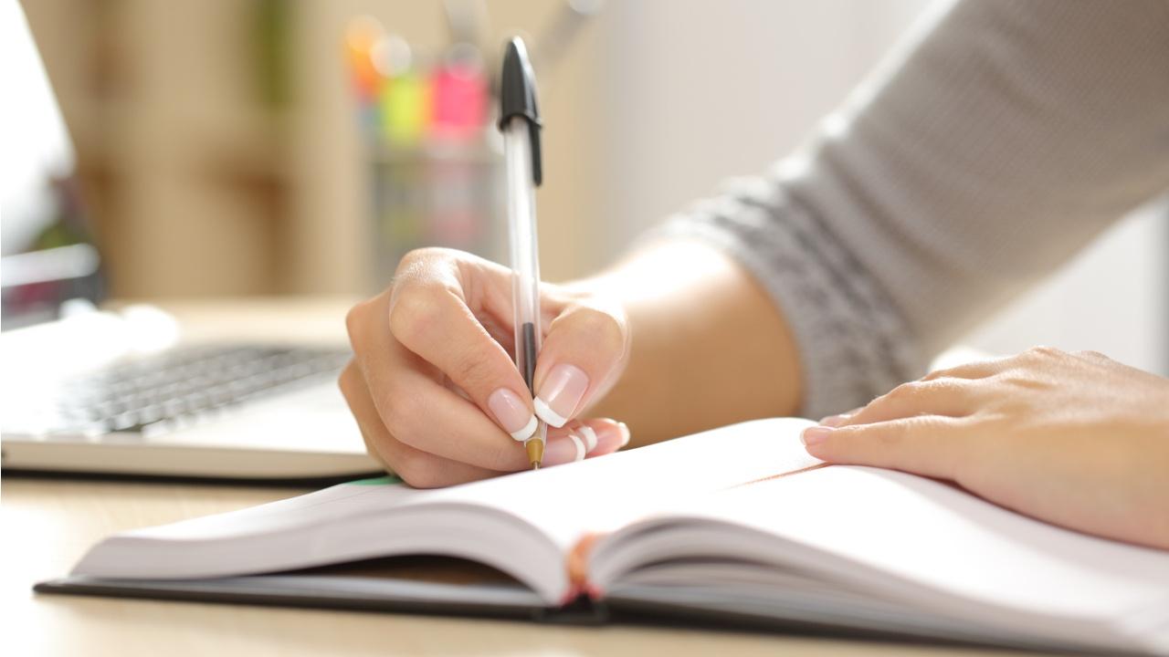 mano escribe con lapicero sobre cuaderno