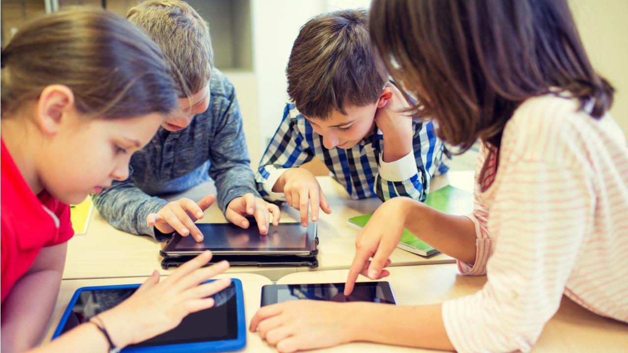 grupo de niños frente a una tablet