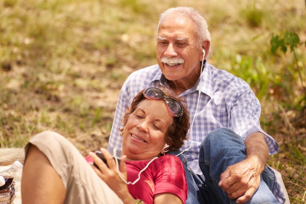 pareja mayor escuchando música al aire libre