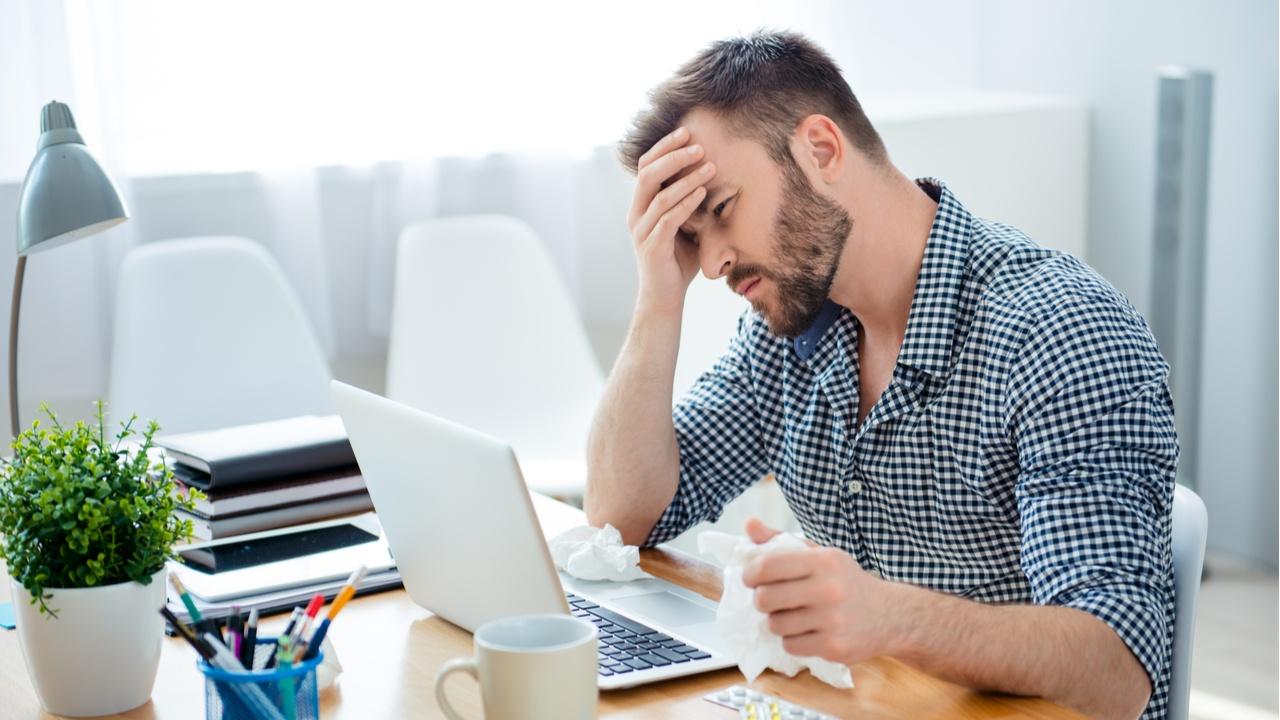 hombre en laptop con dolor de cabeza