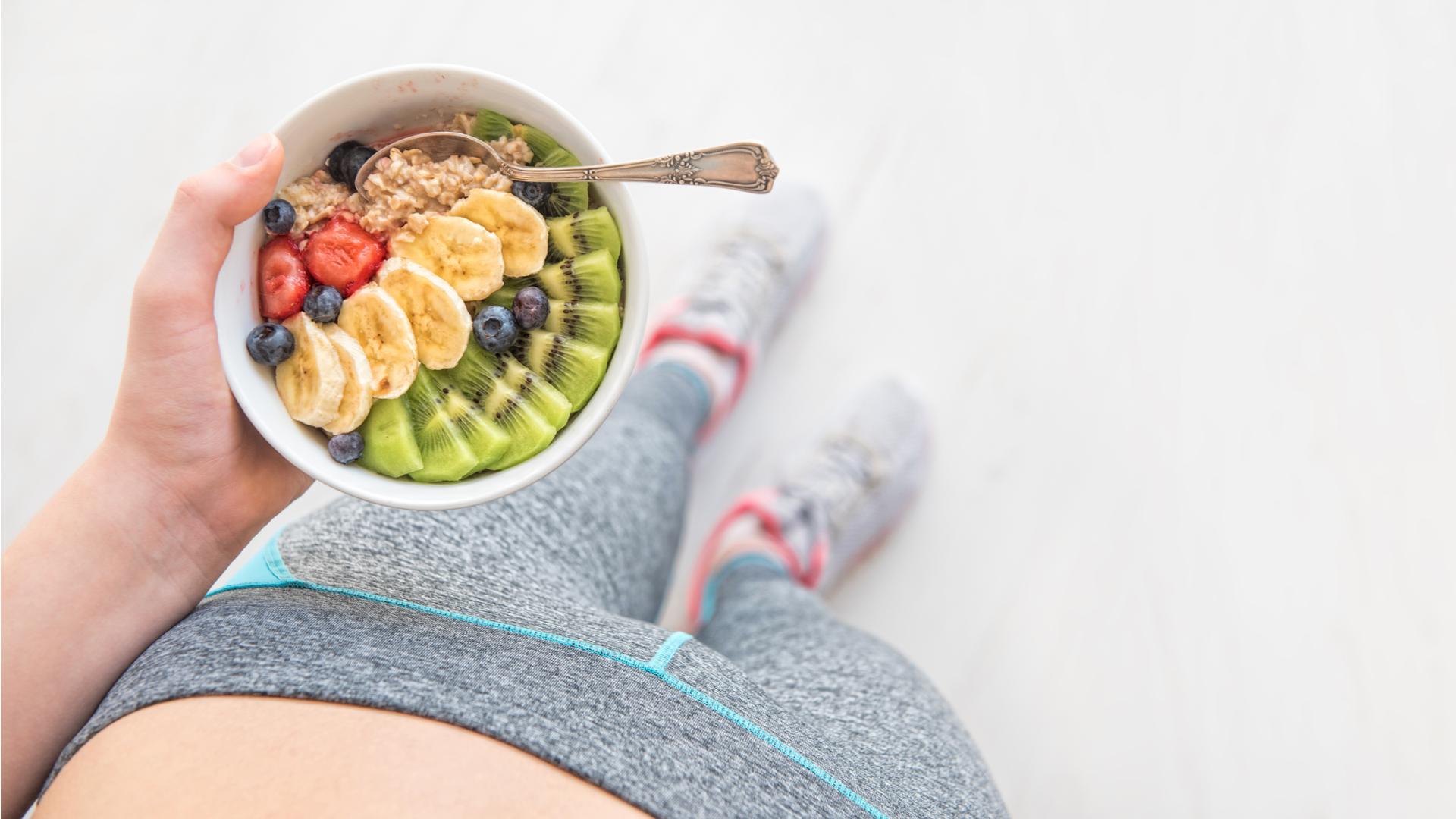 mujer con ropa deportiva comiendo avena con frutas