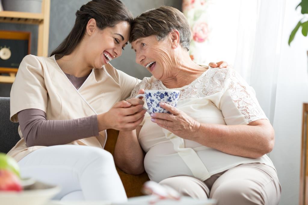 mujer mayor y enfermera riendo